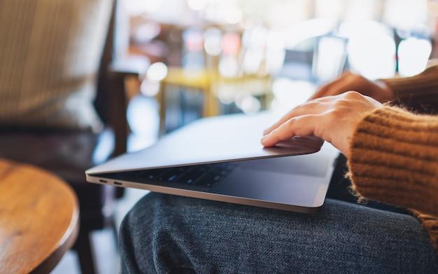 Image en gros plan d'une femme qui ferme et ouvre un ordinateur portable après avoir fini de l'utiliser