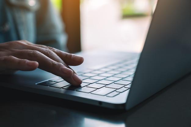 Image en gros plan d'une femme tapant et appuyant sur le doigt sur le clavier de l'ordinateur portable