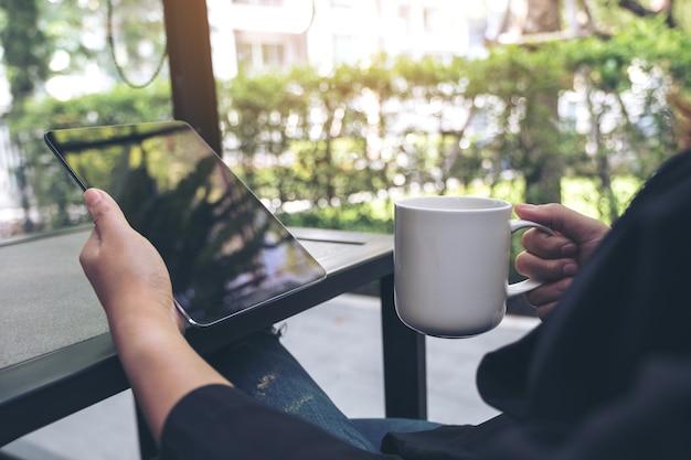 Image gros plan d'une femme tenant et à l'aide de tablet pc tout en buvant du café au café
