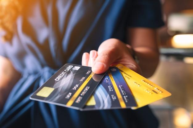 Image gros plan d'une femme tenant et montrant des cartes de crédit