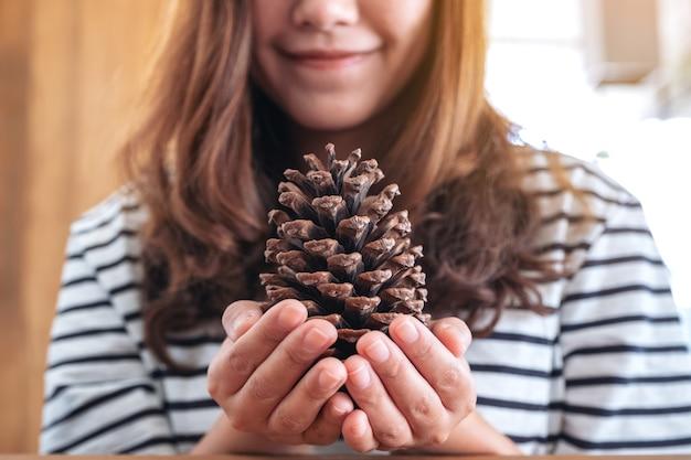 Image gros plan d'une femme tenant une pomme de pin dans ses mains