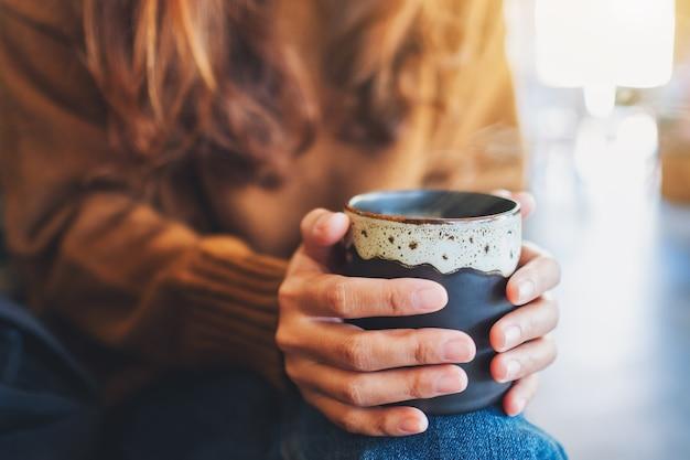 Image gros plan d'une femme tenant une tasse de café chaud