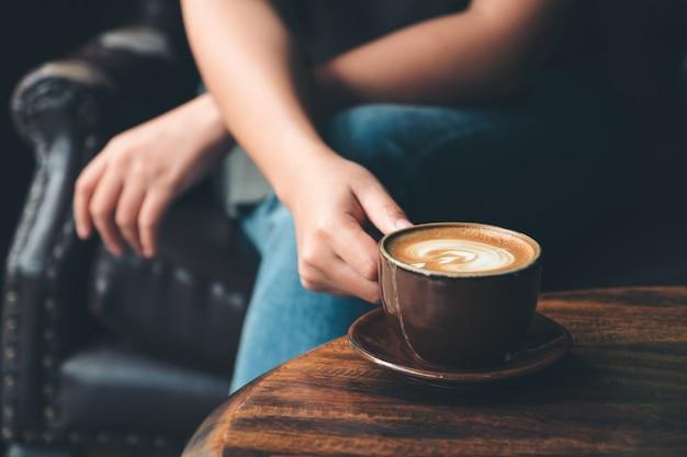 Image gros plan d'une femme tenant une tasse de café sur une table en bois vintage au café