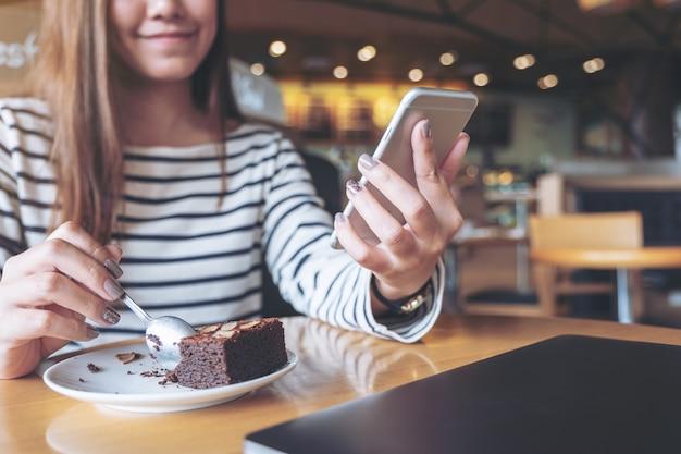 Image gros plan d'une femme tenant, utilisant et regardant un téléphone intelligent tout en mangeant un gâteau brownie au café