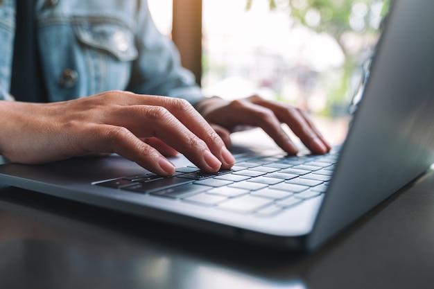 Image en gros plan d'une femme travaillant et tapant sur un clavier d'ordinateur portable