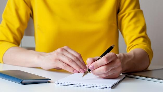 Image en gros plan d'une femme vêtue d'une robe jaune assise à un bureau et écrit quelque chose dans un cahier vierge blanc. entreprise, marketing, concept d'éducation