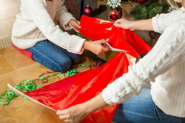 Image en gros plan d'une fille coupant du papier d'emballage rouge pour des cadeaux de noël