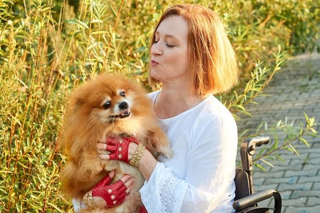 Image en gros plan heureuse femme rousse en fauteuil roulant pour une promenade avec son chien. journée internationale des personnes handicapées