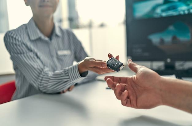 Image en gros plan un homme achète une voiture et reçoit les clés du vendeur.