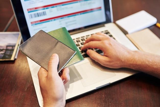 Image en gros plan de l'homme entrant les informations de passeport lors de l'achat de billets d'avion en ligne