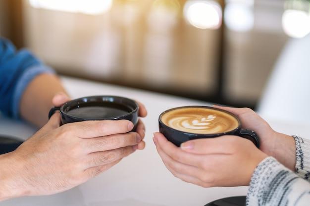 Image en gros plan d'un homme et d'une femme tenant deux tasses de café ensemble