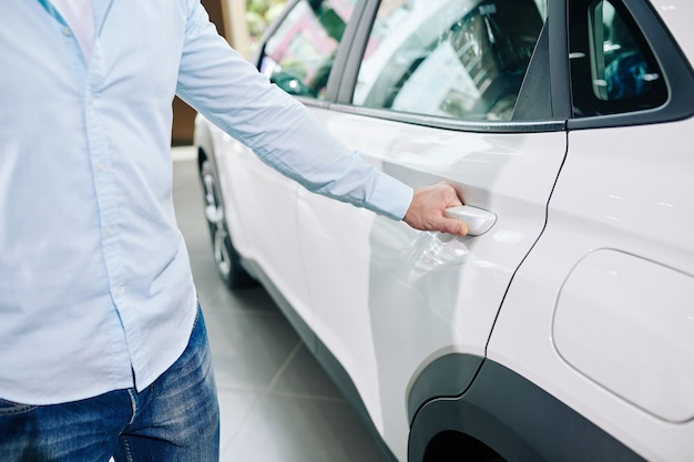 Image en gros plan de l'homme ouvrant la porte arrière de la nouvelle voiture