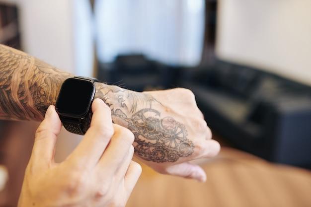 Image en gros plan d'un homme vérifiant les applications sur smartwatch, mise au point sélective