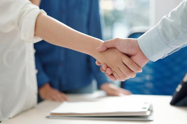 Image en gros plan d'hommes d'affaires se serrant la main après une réunion réussie et la signature d'un contrat