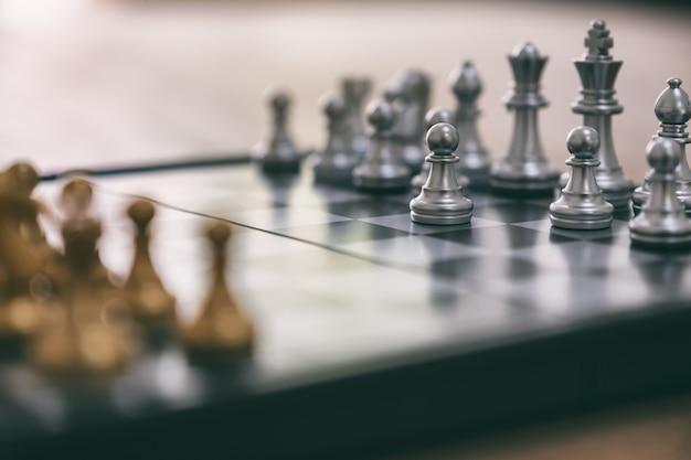 Image en gros plan d'un jeu d'échecs de couleur argent et or sur un échiquier