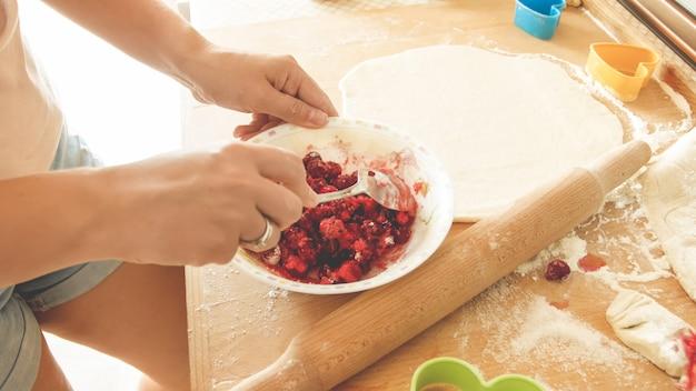 Image en gros plan d'une jeune femme au foyer versant du sucre dans un grand bol avec des baies fgresh tout en faisant de la sauce pour tarte