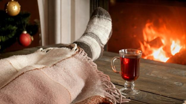 Image gros plan d'une jeune femme en chaussettes de laine allongée sous une couverture à côté d'une cheminée en feu avec un verre de vin chaud