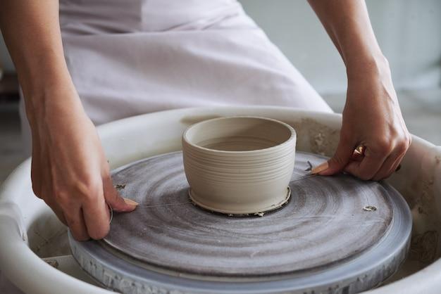 Image en gros plan d'une jeune femme créative coupant un pot en argile avec un outil de fil