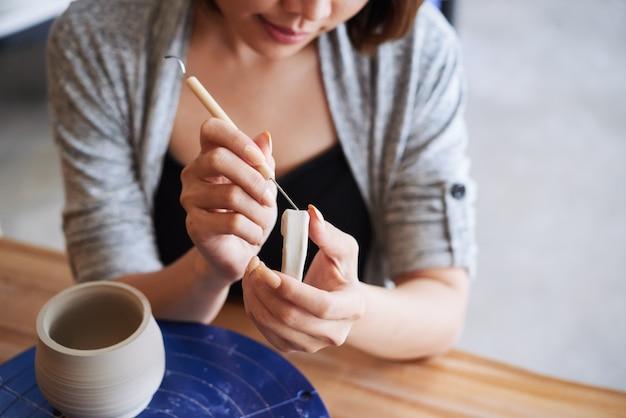 Image en gros plan d'une jeune femme créative sculptant la poignée d'un pot en argile qu'elle a fabriqué sur un tour de potier
