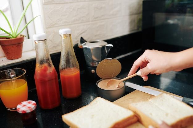 Image en gros plan d'une jeune femme faisant des sandwichs avec du pâté de dinde et du ketchup pour le petit-déjeuner
