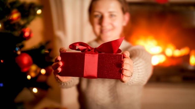 Image en gros plan d'une jeune femme montrant une boîte cadeau de noël rouge à huis clos alors qu'elle était assise à côté d'un arbre de noël et d'une cheminée en feu