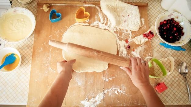 Image En Gros Plan De La Jeune Femme à Rouler La Pâte Avec Un Rouleau à Pâtisserie En Bois Photo Premium