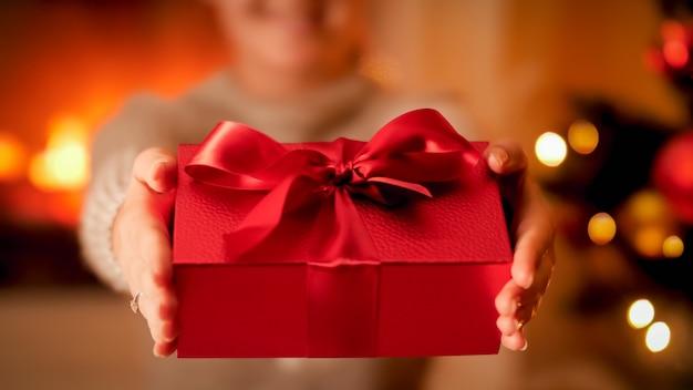 Image en gros plan d'une jeune femme tenant dans les mains une belle boîte rouge pour un cadeau de noël ou un cadeau avec un grand noeud de ruban