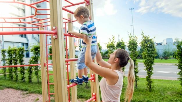 Image en gros plan d'une jeune mère aidant son petit fils à grimper sur de hauts escaliers métalliques dans une aire de jeux pour enfants sportifs