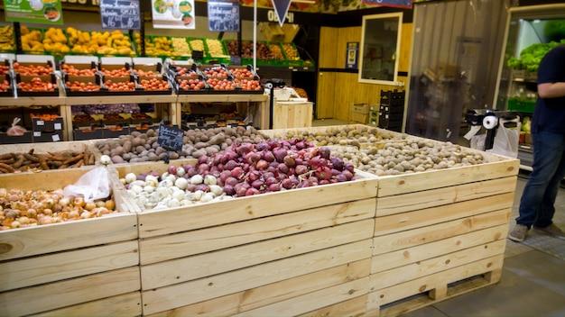 Image en gros plan de légumes frais dans des caisses en bois sur les comptoirs des épiceries