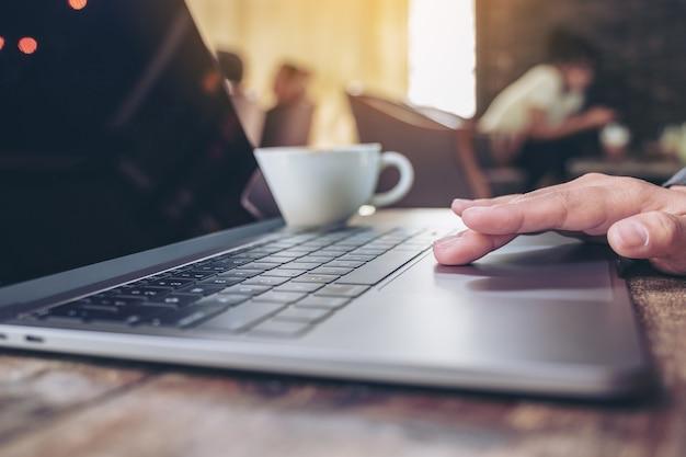 Image gros plan de la main à l'aide et en touchant le pavé tactile d'ordinateur portable avec une tasse de café sur la table en bois