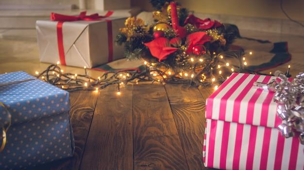 Image gros plan d'une main féminine mettant une boîte-cadeau rouge avec un ruban doré sous l'arbre de noël