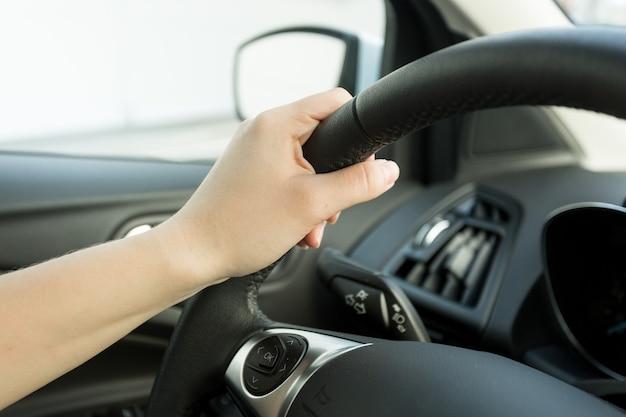 Image gros plan de main féminine tenant le volant de voiture