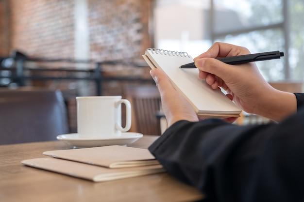 Image gros plan d'une main tenant et écrit sur un cahier vierge avec une tasse de café sur la table au café