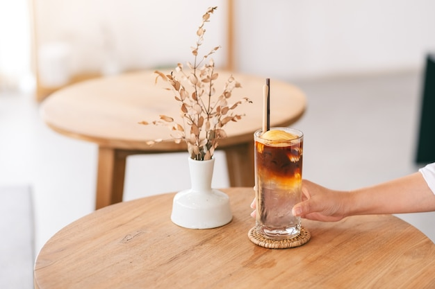Image en gros plan d'une main tenant un verre de café glacé à la noix de coco sur une table en bois dans un café minimal