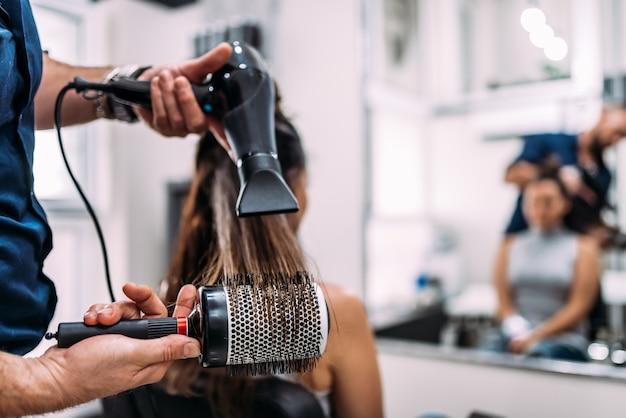 Image gros plan des mains de coiffeurs séchant les cheveux longs avec sèche-cheveux et brosse ronde.