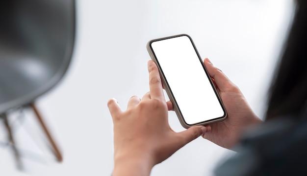 Image gros plan des mains de la femme à l'aide d'un smartphone avec écran vide.