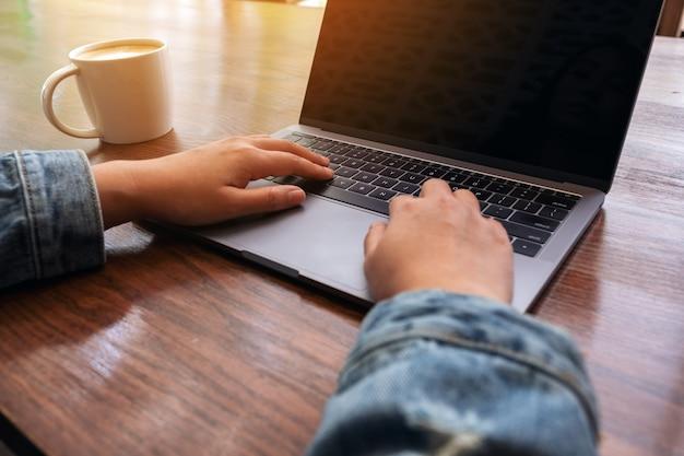 Image gros plan des mains de la femme à l'aide et en tapant sur le clavier d'ordinateur portable sur la table