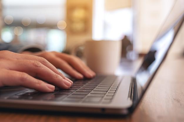 Image gros plan des mains de la femme à l'aide et en tapant sur le clavier de l'ordinateur portable avec une tasse de café sur la table