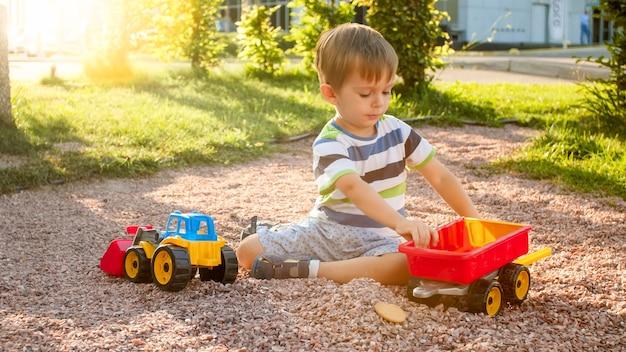 Image en gros plan d'un mignon petit garçon jouant sur le terrain de jeu avec des jouets. enfant s'amusant avec camion, pelle et remorque