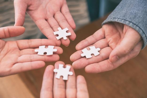 Image en gros plan de nombreuses personnes mains tenant et assemblant un morceau de puzzle blanc