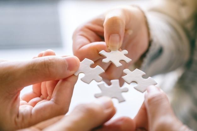 Image en gros plan de nombreuses personnes tenant et assemblant un morceau de puzzle blanc