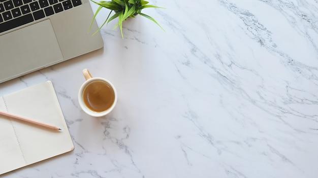 Image en gros plan partie d'un ordinateur portable, y compris une tasse à café, un crayon, un ordinateur portable et une plante en pot mettant sur une table de bureau en marbre.