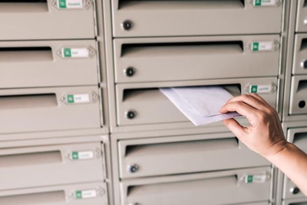 Image gros plan d'une personne insérant une enveloppe dans une boîte aux lettres.