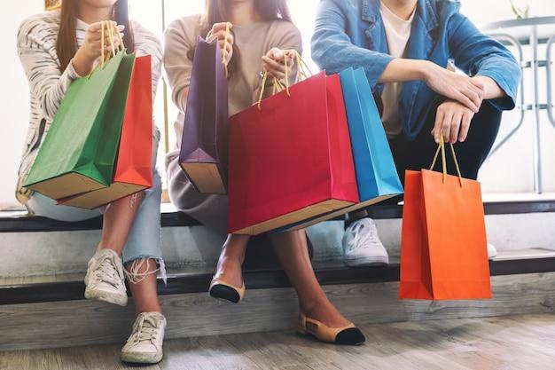 Image en gros plan de personnes assises et tenant ensemble des sacs à provisions