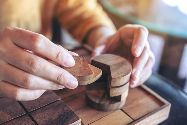 Image gros plan de personnes jouant et construisant un jeu de puzzle en bois rond