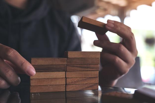 Image gros plan de personnes jouant et construisant un jeu de puzzle en bois