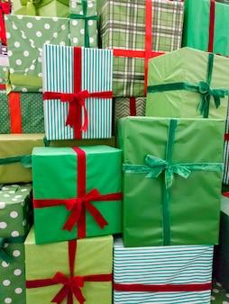 Image gros plan de tas de beaucoup de cadeaux de noël. pile de boîtes vertes avec des rubans rouges avec des cadeaux de nouvel an
