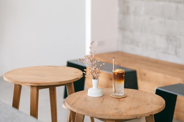 Image en gros plan d'un verre de café glacé à la noix de coco sur une table en bois dans un café minimal