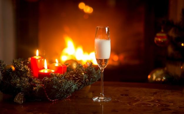 Image en gros plan de verser du champagne pétillant dans un verre de cristal sur une table décorée pour noël