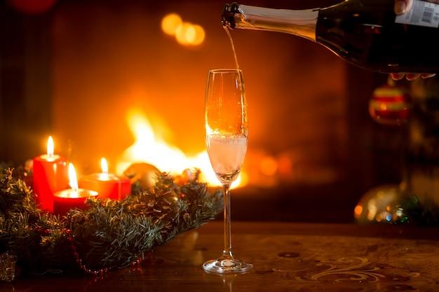 Image en gros plan de verser du champagne pétillant dans un verre de cristal sur une table